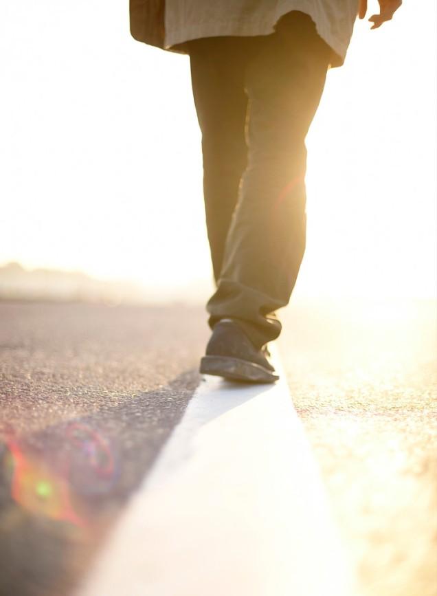 Man Walking Along Line in Road